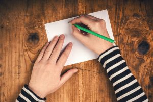A hand writing a formal letter.